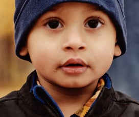 Young child looking adorable in blue hat