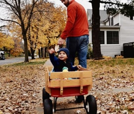 Father pulling his toddler in a wagon in the fall